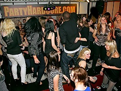 A big group of people, most of them girls, is dancing in a disco....