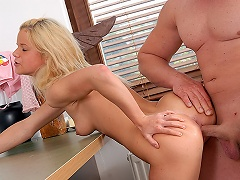 A blonde teenage girl is sitting on top of a desk. A guy who is next...